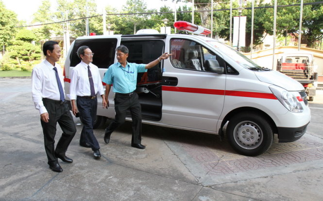 Ông Phan Văn Hà (trái) tiếp nhận xe cứu thương chuyên dụng do Công ty TNHH Xăng dầu Hồng Đức trao tặng - Ảnh: V.TR.