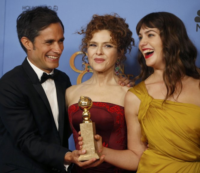 Actors Bernal, Peters and Kirke pose backstage with the award for Best Television Series - Musical or Comedy for