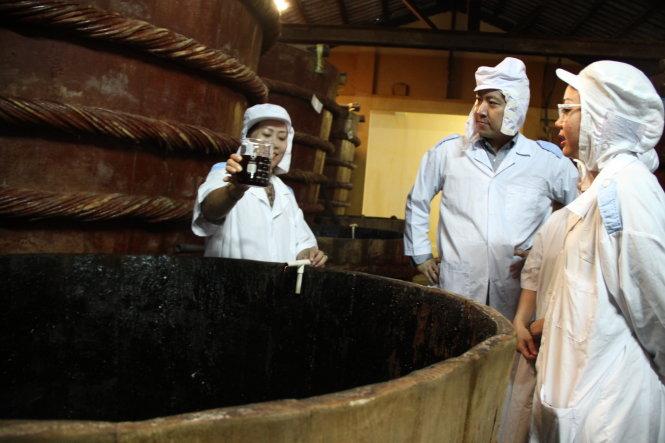 Ông Sasaki Shingo (giữa) tìm hiểu quy trình sản xuất nước mắm Phú Quốc tại nhà thùng Thanh Hà - Ảnh: TẤN ĐỨC