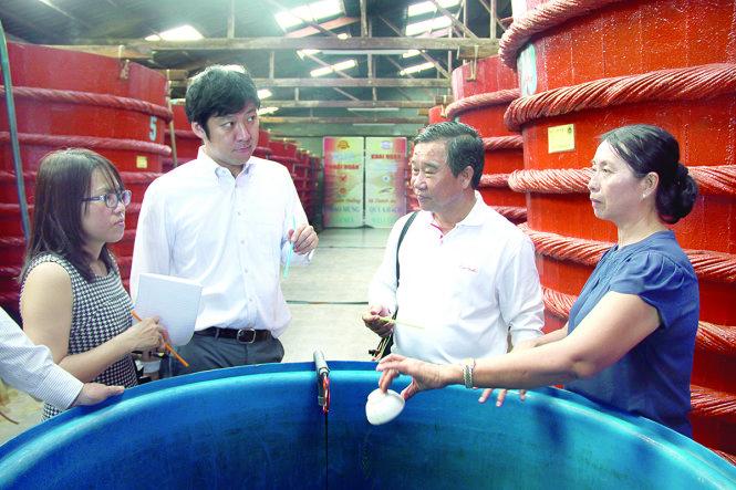 Ông Sasaki Shingo của Tổ chức Thúc đẩy ngoại thương Nhật Bản (thứ hai từ trái sang) tìm hiểu quy trình làm nước mắm Phú Quốc ở nhà thùng Khải Hoàn - Ảnh:Tấn Đức