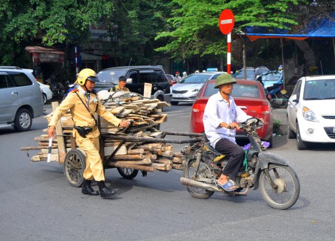CSGT dừng xe để xử lý trường hợp chở hàng cồng kềnh trên đường Trần Nhật Duật (Hà Nội). Phần lớn xe cũ nát được dùng để chở hàng cồng kềnh, gây nguy hiểm cho người đi đường - Ảnh: Nam Trần