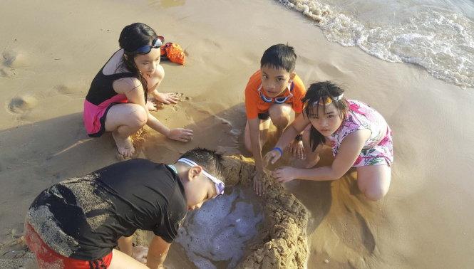 Bốn du khách nhí nghịch cát ven bờ biển resort Vinpearl Phú Quốc - Ảnh: K.NAM Đón 45.000 lượt khách, phú quốc thu 70 tỉ trong 4 ngày lễ Đón 45.000 lượt khách, Phú Quốc thu 70 tỉ trong 4 ngày lễ du lich pq anh 1 1493729032