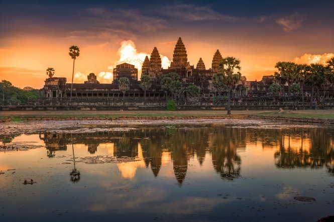 It looks, upon first glance, like a raging fire emerging from behind Cambodia's Angkor Wat temple complex, but rather it's a cloud lit up with the rising sun© Getty Images
