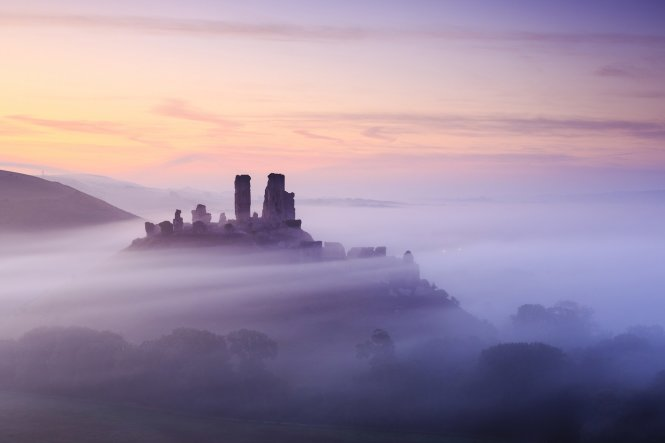 Alternatively, stay closer to home and admire English country scenes like this dawn view of Corfe Castle in Dorset © UIG via Getty Images