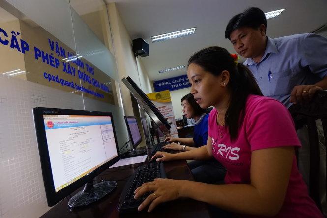 Trong ảnh: người dân Q.8, TP.HCM đăng ký cấp phép xây dựng qua mạng trên trang web cpxd.quan8.hochiminhcity.gov.vn, tại trụ sở UBND Q.8.       -Ảnh: Quang Định