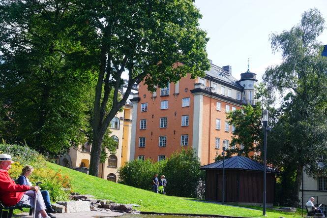 Người già ngồi sưởi nắng, đọc sách báo - hình ảnh thường thấy trên phố ở Stockholm. -Ảnh: c.n.