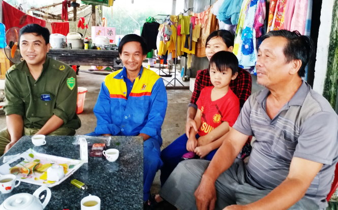 Ông Hữu (phải) cùng anh Hiển (bìa trái) đến thăm gia đình anh Tiến sau khi lũ rút. -Ảnh: TRẦN MAI