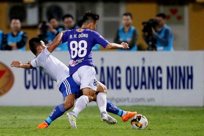 Một pha bóng quyết liệt trong trận Hà Nội (áo xanh) đá bại Quảng Nam 1-0. Ảnh: NAM KHÁNH