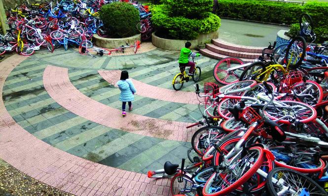 Dịch vụ chia sẻ xe đạp ở Trung Quốc bùng nổ đã dẫn tới các hệ lụy như bãi rác xe đạp này tại Thâm Quyến.-Ảnh: AFP