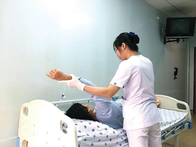 Bệnh nhân được hỗ trợ tập bài tập vai (ảnh chụp tại bv Đại học Y dược TP.HCM). Ảnh: Huỳnh Thị Minh Thùy