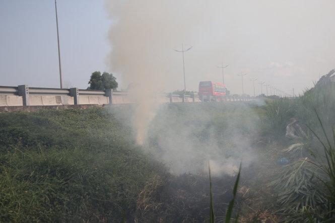 Người dân đốt cỏ cạnh đường cao tốc TP.HCM - Trung Lương đoạn qua tỉnh Tiền Giang, ngày 5-4-2018. Ảnh: Mậu Trường