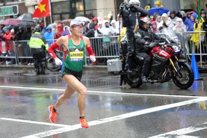Nhà vô địch Marathon Boston 2018 - Yuki Kawauchi trên đường chạy, và bên đường là lá cờ VN - chỉ dấu cho biết người Việt chính thức dự giải. Ảnh trên báo Boston Herald