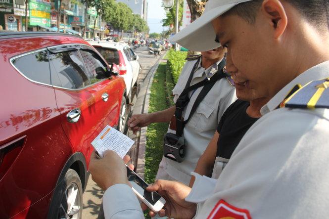 Lực lượng kiểm tra quy tắc đô thị Q.Hải Châu, TP Đà Nẵng mất nhiều thời gian để hướng dẫn và thu phí đậu đỗ xe qua phần mềm thông minh. Ảnh: TRƯỜNG TRUNG