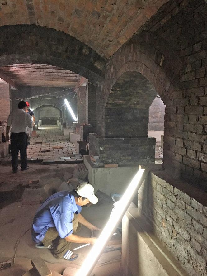 Công nhân lát gạch cho tầng hầm. Khi hoàn thành trùng tu, đây sẽ là khu triển lãm.