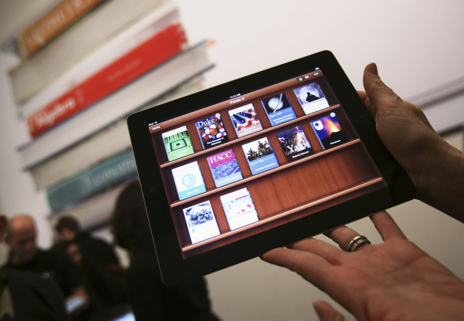 A woman holds up an iPad with the iTunes U app after a news conference introducing a digital textbook service in New York in this January 19, 2012, file photo. The U.S. Justice Department has warned Apple and five major U.S. publishers that it plans to sue them, accusing them of colluding to raise the prices of electronic books, a person familiar with the probe said on March 8, 2012.      REUTERS/Shannon Stapleton/Files (UNITED STATES - Tags: SOCIETY EDUCATION SCIENCE TECHNOLOGY BUSINESS) - RTR2Z1Q3