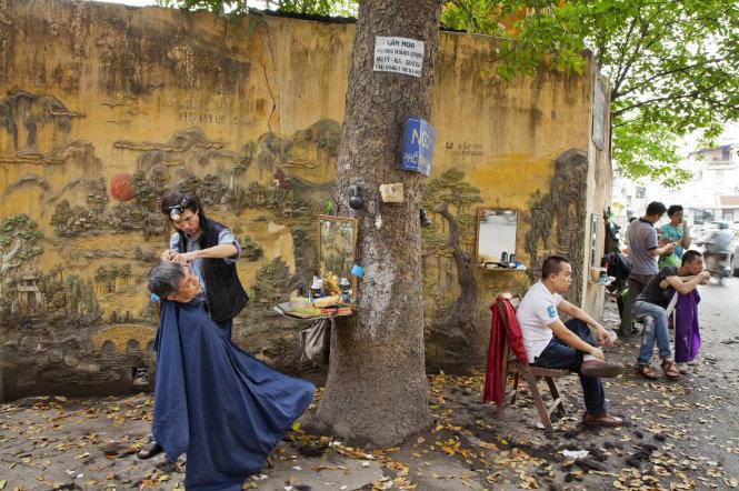 """Thợ cắt tóc, 2014. Anh Bùi Phạm Quát (trái) vẽ những phù điêu trên tường để """"làm đẹp"""" nơi làm việc hàng ngày của mình"""