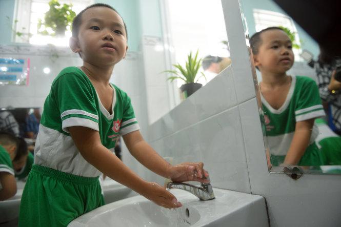 Các em nhỏ được hướng dẫn rửa tay sạch sau khi chơi chung đồ chơi với các bạn để phòng ngừa bệnh tay chân miệng. Ảnh: DUYÊN PHAN