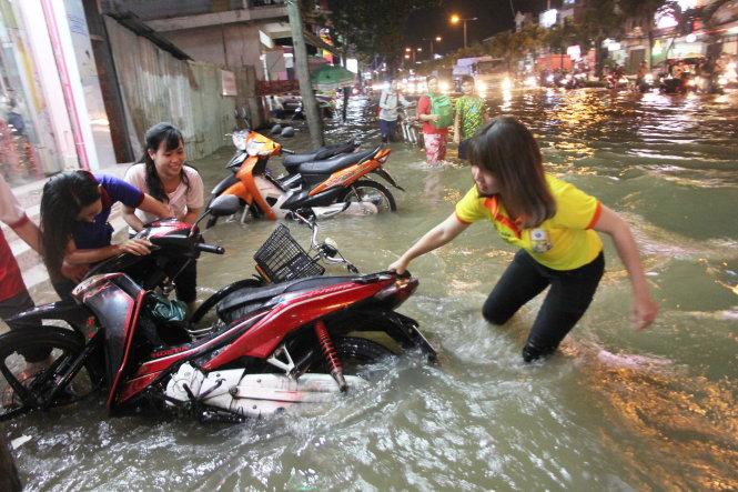 """Người dân TP Cần Thơ phải """"vật lộn"""" với ngập đường trong đợt triều cường giữa tháng 10-2018. Ảnh: CHÍ QUỐC"""