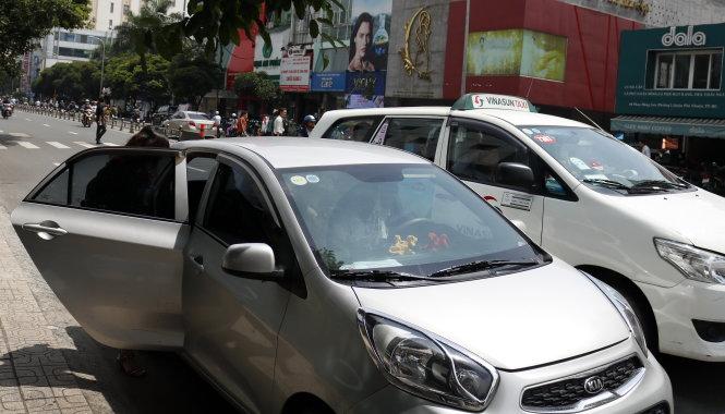 Tài xế taxi Vinasun và Grab đón khách trên đường Phan Đăng Lưu, phường 6, quận Bình Thạnh. Ảnh: NGỌC PHƯỢNG