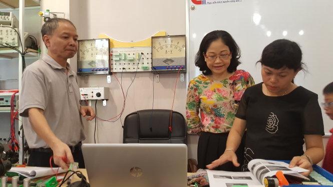 Thầy Mai Văn Túc trao đổi kỹ năng thực hiện bài thí nghiệm vật lý với một số giáo viên. ảnh: Nguyễn Yến