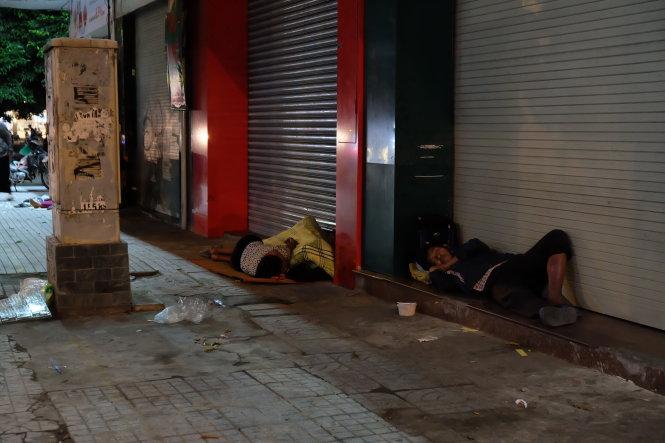 Khi hàng quán đóng cửa cũng là lúc nhiều người chọn cho mình một chỗ ngủ dưới mái hiên (ảnh chụp tại đường Phan Đăng Lưu, quận Phú Nhuận)  Ảnh: CÔNG TRIỆU