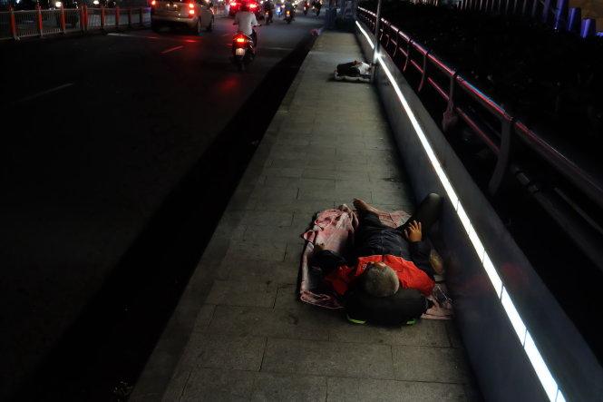 Hai người đàn ông chọn cầu Kiệu (nối quận 1 và quận Phú Nhuận) làm chỗ ngả lưng qua đêm. Ảnh: Vũ Thủy