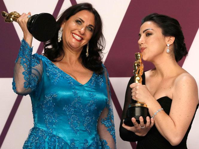 Nữ đạo diễn Rayka Zehtabchi (phải) và nhà sản xuất Melissa Berton vui mừng với tượng vàng Oscar. Ảnh: Reuters