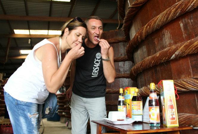 Du khách nước ngoài thích thú xen lẫn một chút hồi hộp lần đầu nếm thử nước mắm Phú Quốc. Ảnh: D.KHÁNH