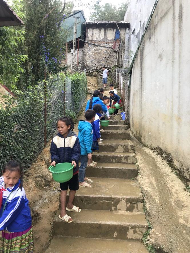 Các học sinh ở Trường dân tộc nội trú tại Sa Pa đang chuyền nước sạch do chính quyền phân phát với số lượng hết sức khiêm tốn. Ảnh: Bá Hiếu