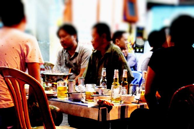 Người dân uống bia trên đường Hoàng Sa, quận 3, TP.HCM. Ảnh: TỰ TRUNG