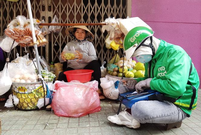 Từ chỗ bán hàng rong với đôi quang gánh (ảnh trái), bà Nguyễn Thị Cảnh (quê Bình Định) 2 năm nay phải tăng cường người và thuê thêm mặt bằng để phục vụ người mua qua mạng (ảnh phải). Ảnh: NGỌC HIỂN