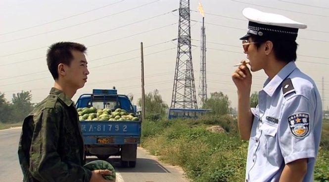 Hoành Lí mặc sắc phục, chặn đường xe tải kiếm tiền