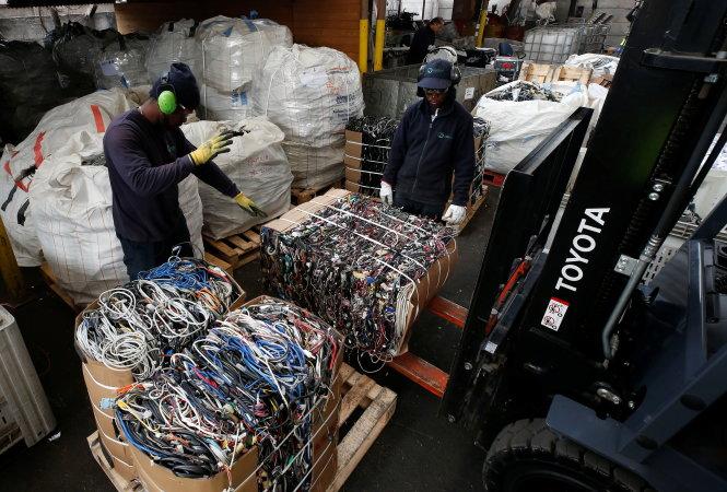 Công nhân di chuyển các kiện dây cáp phế liệu tại một nhà máy xử lý rác điện tử và giấy ở Santiago, Chile. Ảnh: Reuters