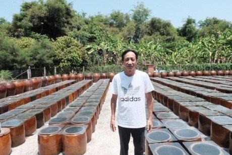 Anh Lê Kim Sơn ở sân ủ tương trước ngôi nhà tổ tiên để lại. Ảnh: Pha Lê