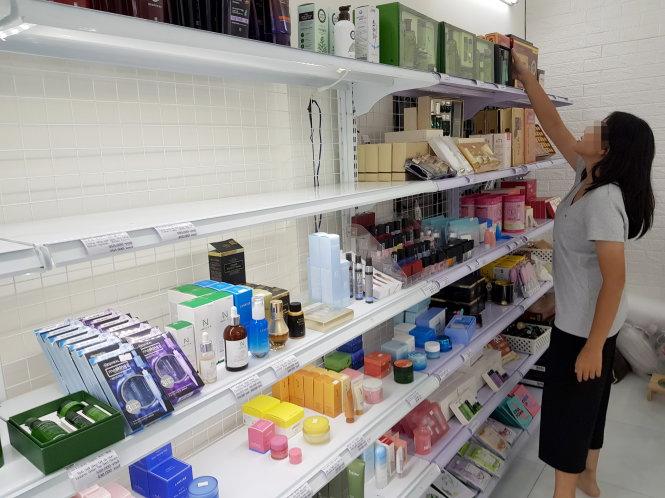 Nữ nhân viên của một cửa hàng chuyên bán hàng xách tay Hàn Quốc trưng bày các sản phẩm lên kệ. Ảnh: NGỌC HIỂN