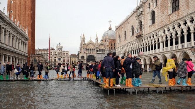 Venice ngập mà không hỗn loạn trong trận bão năm 2018. Thành phố đã quen với chuyện sống với nước ngập và du khách cũng không lạ về việc này. Ảnh: REUTERS