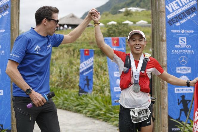 David Lloyd, giám đốc thể thao Topas Travel, chúc mừng VĐV Nguyễn Tiến Hùng vô địch 100km ở vạch đích. Ảnh: LƯU KHƯƠNG