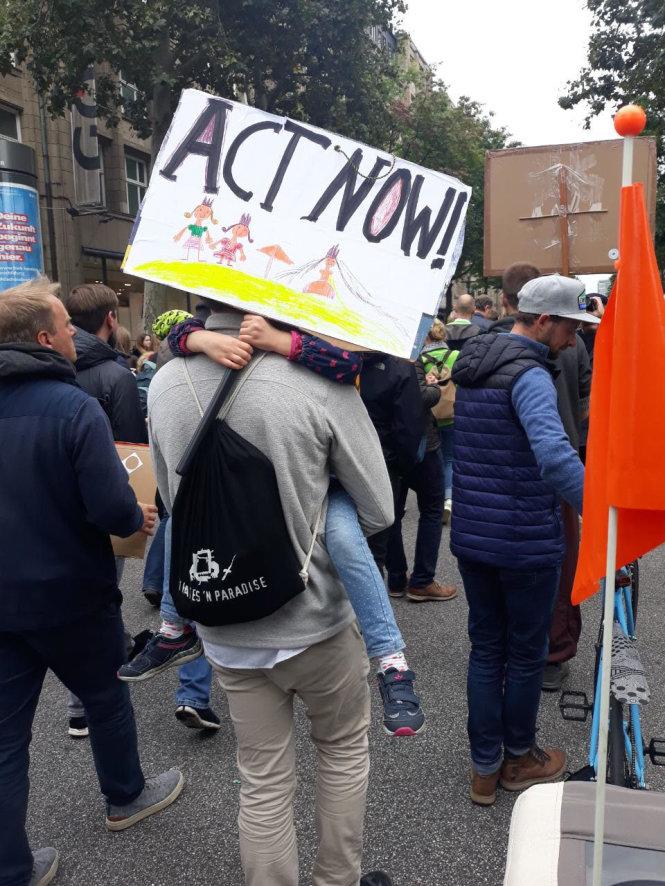 Hai cha con cùng tham gia tuần hành tại Hamburg (Đức) hôm 20-9, tấm biển em bé cầm có dòng chữ