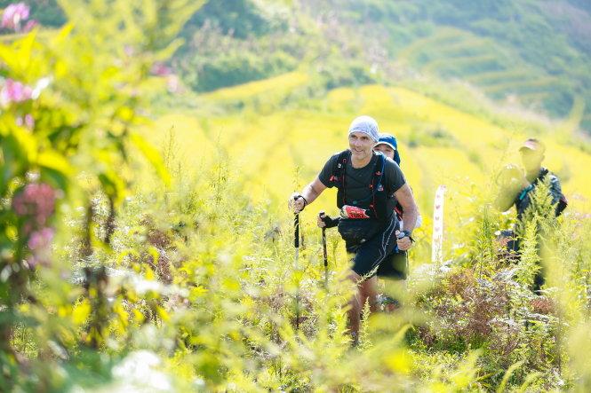 Một VĐV nước ngoài trên đường chinh phục cự ly 70km, đằng sau là ruộng bậc thang đang vào mùa lúa chín. Ảnh: LƯU KHƯƠNG