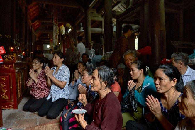 Dùng hai đồng xu để cầu xin sự linh ứng và dự báo về may mắn trong một nghi lễ diễn ra dịp Vu Lan tại chùa Phổ Minh (Nam Định). Ảnh: Nicolas Cornet