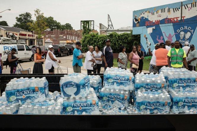 Người dân xếp hàng chờ lấy nước đóng chai ở Newark. Ảnh: New York Times