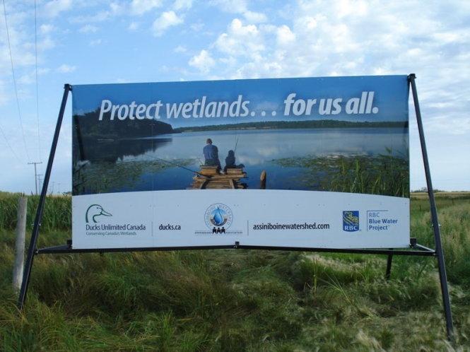 """Biển truyền thông kêu gọi người dân bảo vệ nguồn nước """"vì tất cả chúng ta"""" của Hiệp hội quản lý đầu nguồn Assiniboine được đặt tại nhiều nơi ở Canada. Ảnh: Assiniboine Watershed"""