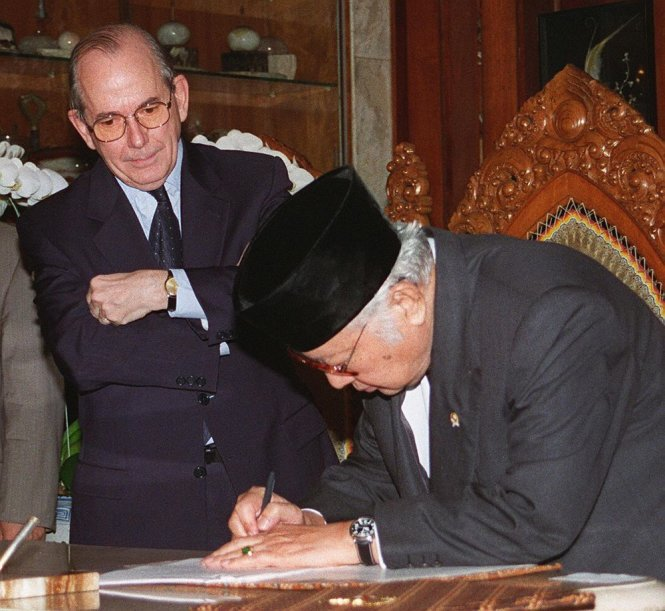 Tấm hình nổi tiếng: tổng giám đốc IMF Michel Camdessus khoanh tay chứng kiến tổng thống Indonesia Suharto ký văn kiện xin cứu trợ.-Ảnh: Bloomberg