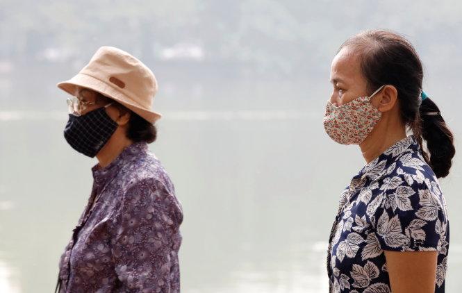 Hai người phụ nữ mang khẩu trang đi bộ thể dục ở hồ Hoàn Kiếm, Hà Nội ngày 2-10-2019. Ảnh: REUTERS