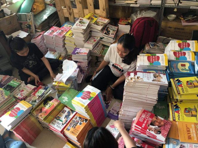 Các bạn trẻ cặm cụi trong kho sách của CNYT để gửi đi những hạt mầm ước mơ - Ảnh: CNYT
