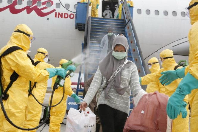 Nhân viên y tế phun thuốc khử trùng cho những công dân Indonesia được di tản khỏi Vũ Hán trở về nước. Họ sẽ được cách ly ở căn cứ quân đội trên đảo Natuna. Ảnh: REUTERS