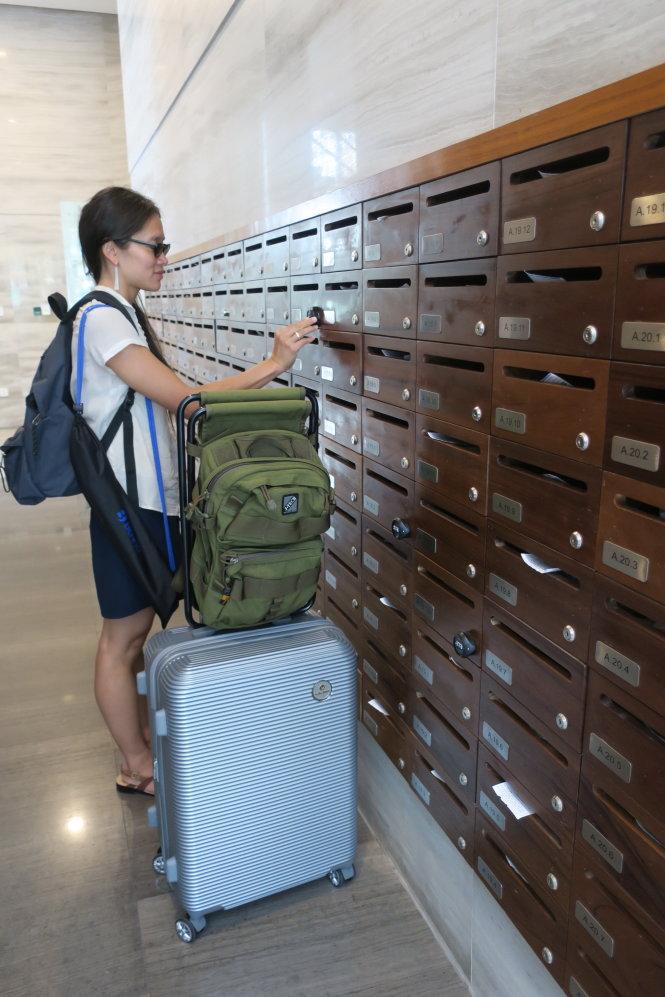 Có khi từ lúc thuê căn hộ dạng Airbnb đến lúc trả thì khách có thể không gặp mặt chủ nhà. Trong ảnh: một khách Việt kiều Pháp mở tủ bằng mã số để lấy thẻ thang máy và password để lên phòng mà không cần gặp chủ nhà. Ảnh: T.T.D. (ảnh chụp tháng 3-2020)