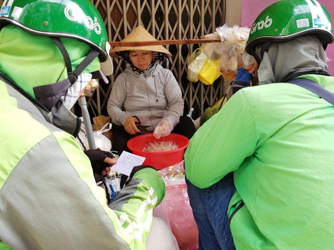 """Gánh hàng rong của một phụ nữ bán bánh tráng trộn tại quận Phú Nhuận bị """"bao vây"""" bởi các shipper công nghệ.  Ảnh: NGỌC HIỂN"""