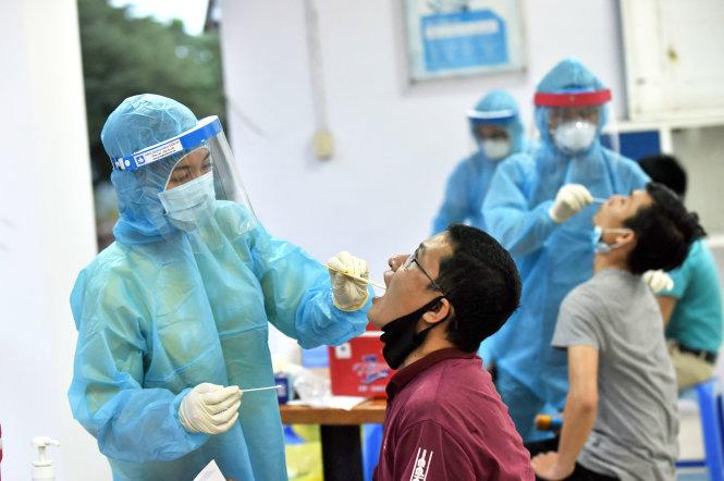 Công nhân lưu trú thuộc Khu chế xuất Tân Thuận được nhân viên y tế lấy dịch ở họng và mũi (ảnh chụp tháng 4-2020). Ảnh: DUYÊN PHAN