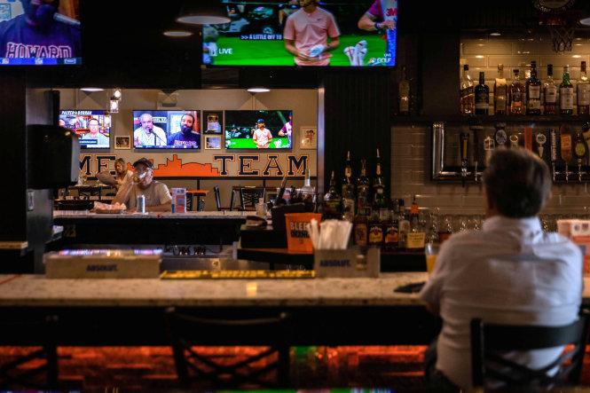 Khách ngồi trong quán rượu vắng tanh ở New York, Mỹ ngày 22-7-2020. Ảnh: REUTERS